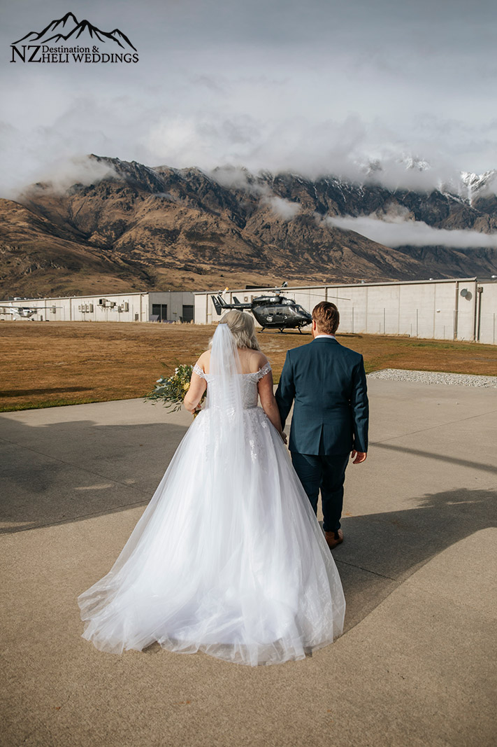 bride and groom walking to helicopter